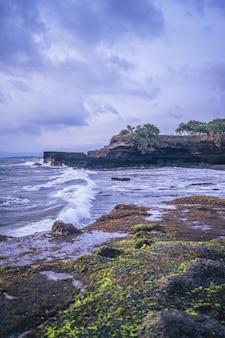 Vertikaler schuss eines ozeanufers mit klippen an einem bewölkten tag