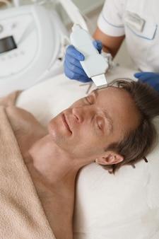 Vertikaler schuss eines reifen mannes, der ultraschallhautreinigung durch kosmetikerin erhält