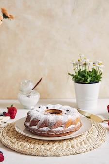 Vertikaler schuss eines ringkuchens mit früchten und pulver auf einem weißen tisch