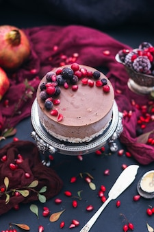 Vertikaler schuss eines schokoladenkuchens mit frischen beeren und granatapfelkernen darauf