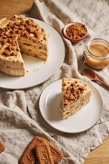 Vertikaler schuss eines stückes des köstlichen lotusplätzchenkuchens mit karamell mit keksen auf dem tisch