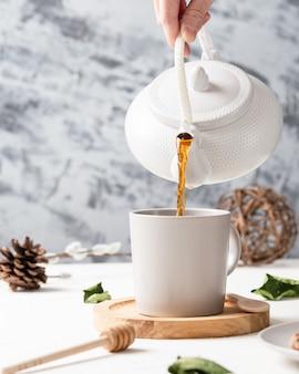 Vertikaler schuss eines tees, der von einem kessel zu einer weißen tasse mit einem holzlöffel fließt