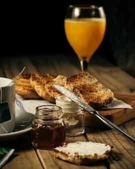 Vertikaler schuss honig und orangensaft und ein messer, das sahne auf eine scheibe brot auf einem tisch verteilt