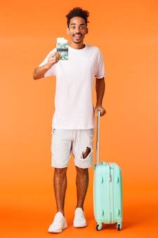 Vertikaler schuss in voller länge fröhlicher auftakt, afroamerikanischer mann mit gepäck, der einen reisepass mit zwei flugtickets hält, amüsiert lächelt, ins ausland fliegt, in den urlaub fährt, orangefarbener hintergrund steht.