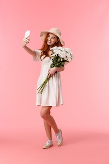 Vertikaler schuss in voller länge reizende, romantische und dumme rothaarigefrau, die schönen frühlingstag genießt, blumenstraußblumen hält und das selfie auf dem smartphone, das lächeln entzückt nimmt