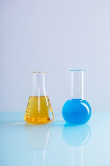 Vertikaler schuss von erlenmeyerkolben mit gelber flüssigkeit und einem rundkolben mit blauer flüssigkeit in einem labor