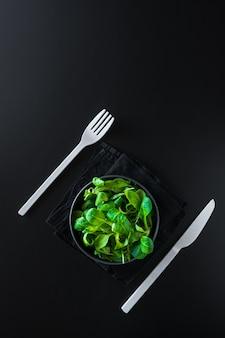 Vertikaler schuss von grünen blättern canonigos und rucula, um salate zu machen