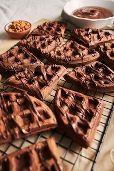 Vertikaler schuss von köstlichen schokoladenwaffeln auf einem netz auf dem tisch nahe den bestandteilen