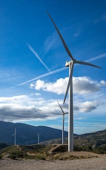 Vertikaler schuss von mehreren weißen elektrischen windmühlen auf einem hügel