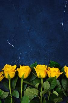 Vertikaler schuss von oben von gelben rosen auf dunkelblauem hintergrund