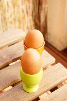 Vertikaler schuss von zwei eiern in den bechern auf einem holztisch