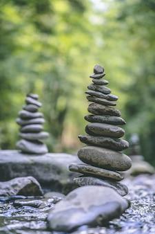 Vertikaler schuss von zwei steinpyramiden, die auf einem flusswasser ausgeglichen sind