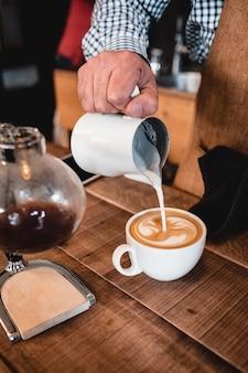 Vertikaler schussmann, der milch in cappuccino gießt