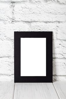 Vertikaler schwarzer fotorahmen auf holztisch. modell mit textfreiraum