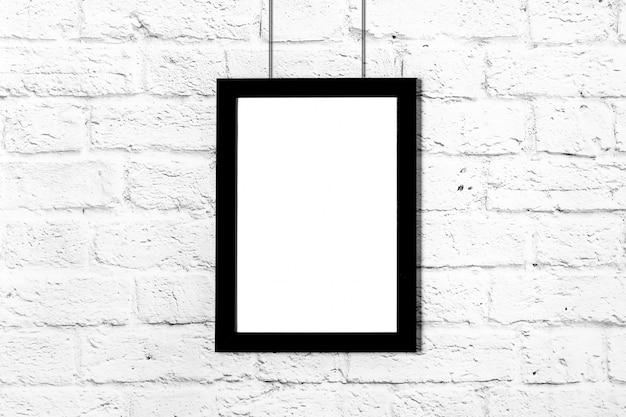 Vertikaler schwarzer fotorahmen, der an der backsteinmauer hängt. modell mit textfreiraum.