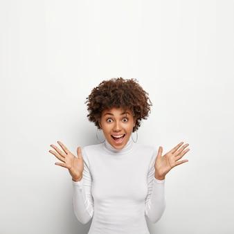 Vertikales bild der aufgeregten freudigen lockigen frau breitet handflächen aus und sieht glücklich aus, reagiert auf teures geschenk, steht allein gegen weiße wand, trägt runde ohrringe, poloneck