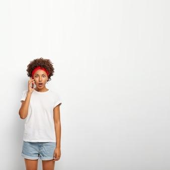 Vertikales bild der betäubten jungen frau hat telefongespräch mit schwester, findet schockierende nachrichten heraus