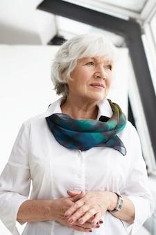 Vertikales bild der charmanten eleganten europäischen großmutter, die ordentliche edle kleidung und accessoires trägt, die zeit drinnen verbringen, über etwas nachdenken und mit nachdenklichem ernstem ausdruck wegschauen
