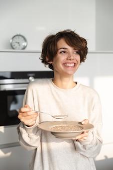 Vertikales bild der fröhlichen brünetten frau, die abendessen und wegschaut, während sie an der küche steht