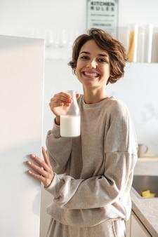 Vertikales bild der lächelnden brünetten frau, die milch in der küche trinkt