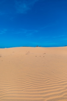 Vertikales bild der schönen sanddünen von mui ne, vientam unter einem klaren blauen himmel Kostenlose Fotos