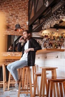 Vertikales bild des bärtigen mannes, der auf bar mit telefon sitzt