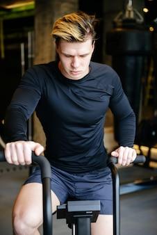 Vertikales bild des ernsten muskulösen mannes unter verwendung des sich drehenden fahrrads