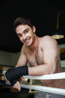 Vertikales bild des glücklichen boxers, der im boxring entspannt
