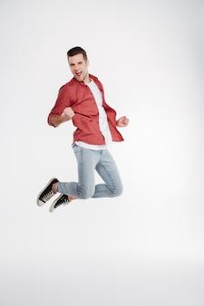 Vertikales bild des glücklichen mannes, der im studio springt