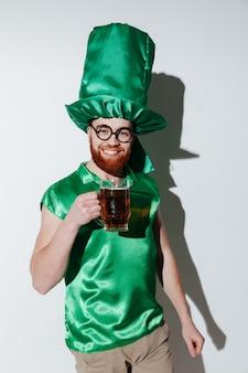 Vertikales bild des glücklichen mannes im st.patriks kostüm, das bier hält