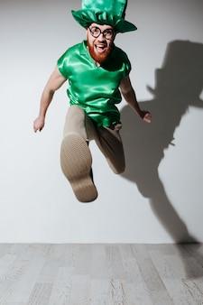 Vertikales bild des glücklichen mannes im st.patriks kostüm