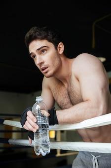 Vertikales bild des jungen boxers, der im boxring sich entspannt
