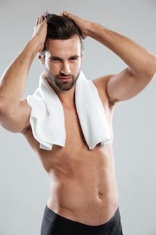 Vertikales bild des jungen muskulösen mannes