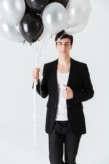 Vertikales bild des lächelnden mannes, der luftballons hält