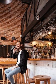 Vertikales bild des mannes, der auf bar sitzt