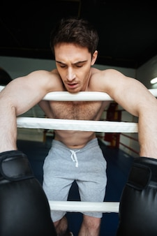 Vertikales bild des müden boxers, der im boxring sich entspannt