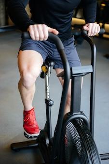 Vertikales bild des muskulösen mannes unter verwendung des sich drehenden fahrrads