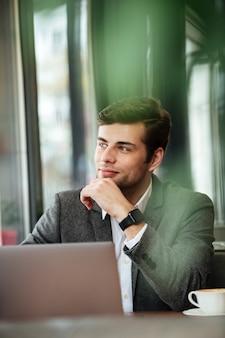 Vertikales bild des nachdenklichen geschäftsmannes sitzend durch die tabelle im café mit laptop-computer und weg schauend