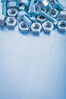 Vertikales bild des raumes von metallbolzen und -muttern auf metallischem hintergrundkonstruktionskonzept kopieren