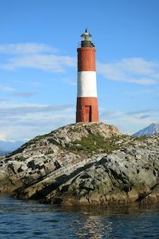 Vertikales bild des roten und weißen gestreiften les eclaireurs-leuchtturmes auf felsigen inseln, spürhundkanal, ushuaia, argentinien