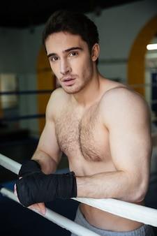Vertikales bild des ruhigen boxers, der im boxring sich entspannt