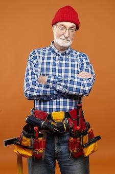 Vertikales bild des selbstbewussten älteren handwerkers mit werkzeuggürtel mit allen instrumenten, die arme auf seiner brust kreuzen.