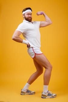 Vertikales bild des sportlers, der bizeps zeigt