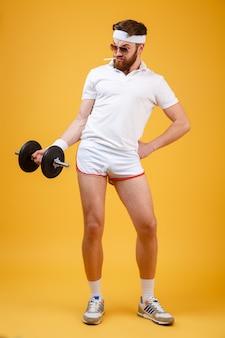 Vertikales bild des sportlers, der hantel hält