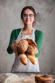 Vertikales bild des weiblichen bäckers, der tasche mit brot zeigt