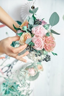 Vertikales bild des weiblichen floristen bei der arbeit. verschiedene blumen im blumenstrauß anordnen. draufsicht. ein lehrer für floristik in meisterklassen oder kursen. professionelles, florales konzept. kopieren sie platz für design