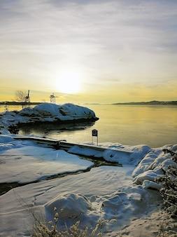 Vertikales bild einer insel, die im schnee bedeckt ist, der durch das meer während des sonnenuntergangs in norwegen umgeben ist