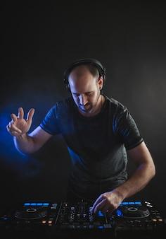 Vertikales bild eines männlichen dj, der unter den blauen lichtern in einem studio arbeitet