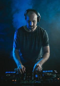 Vertikales bild eines männlichen dj, der unter den lichtern gegen eine dunkelheit arbeitet