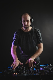 Vertikales bild eines männlichen dj, der unter den lichtern gegen eine dunkelheit in einem studio arbeitet